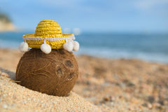 Coconut with sombrero at the beach. Tropical coconut at the Spanish beach with yellow sombrero Royalty Free Stock Photography