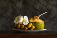 Coconut with southern langsat ornamated with plumeria Royalty Free Stock Image