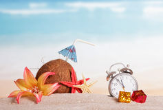 Coconut, starfish, flower, gifts alarm clock in sand against sea. Royalty Free Stock Images