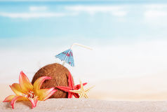 Coconut, starfish and flower in the sand against sea. Royalty Free Stock Photos