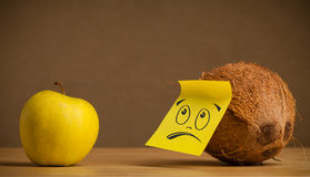 Coconut with sticky post-it note looks sadly at apple Stock Image