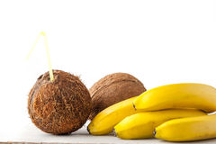 Coconut with straw and bananas on the white table Stock Photo