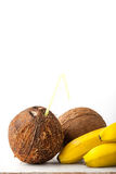 Coconut with straw and bananas on the white table vertical Stock Image