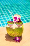 Coconut with straw, colourful sunglasses and orchid flower on th Royalty Free Stock Image