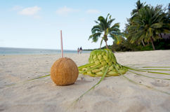 Coconut and sun hat on the sandy sea shore Stock Photos