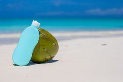 Coconut and suncream on white sand Royalty Free Stock Photos