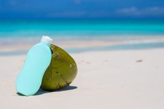Coconut and suncream on white sandy beach Stock Image
