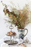 Coconut sweets on vintage dessert stand with wild flowers bouquet Stock Photo
