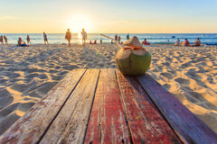 Coconut on the table at sunset beach in Thailand Stock Image