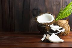 Coconut topview such as coconut half and coconut pieces and leaf on wooden table. royalty free stock image