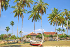 Coconut trees and wooden boat under blue sky Stock Photo