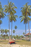 Coconut trees and wooden boat under blue sky Stock Photos