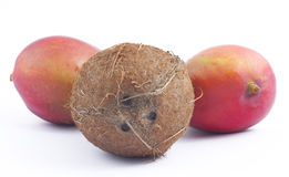Coconut and two mangos on white background. (focus on coconut Royalty Free Stock Photo