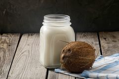 Coconut vegan milk non dairy in jar and coconut on dark wooden table. Fresh organic coconut milk or water, close up.  stock photo