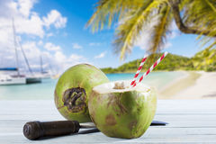 Coconut on wood, cleaver and drinking straws, Caribbean beach Royalty Free Stock Photo