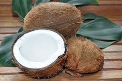 Coconuts. Coconut open on a leaf on wooden background Royalty Free Stock Photography
