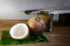Coconuts on banana leaf and coconut grater Stock Photos