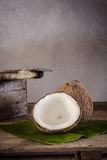 Coconuts on banana leaf and coconut grater Royalty Free Stock Images