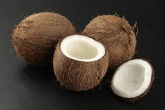 Coconuts on black background. Two whole coconuts and one opened photographed on black background Royalty Free Stock Images