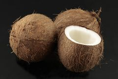 Coconuts on black background. Whole coconuts and one opened photographed on black background Royalty Free Stock Photos