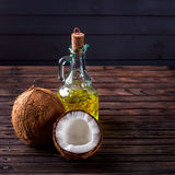 Coconuts a bottle of oil on a dark wooden background. royalty free stock photography