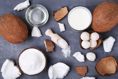 Coconuts. With candies and bottle of milk on grey wooden table Stock Photo