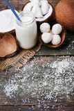 Coconuts with candies. And bottle of milk on wooden table Royalty Free Stock Images