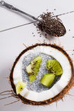Coconuts with chia pudding. Chia seeds pudding with kiwi fruits in the shell of a coconut on white wooden background. Flat lay Stock Images