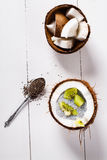 Coconuts with chia pudding. Chia seeds pudding with kiwi fruits in the shell of a coconut on white wooden background. Flat lay Stock Photo