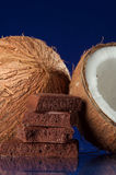 Coconuts and Chocolate. Coconuts and large chunks of chocolate. One coconut is cut in half Stock Image