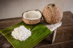 Coconuts and coconut flakes on banana leaf and coconut grater Royalty Free Stock Images