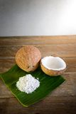 Coconuts and coconut flakes on banana leaf Royalty Free Stock Photo