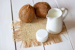 Coconuts and coconut milk in a metal pot. Wooden background royalty free stock photography