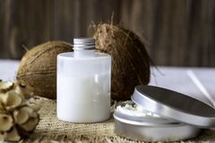 Coconuts and coconut oil in a metal pot. Wooden background stock photo