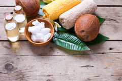 Coconuts, coconut oil and towels on  vintage wooden background. Stock Photos