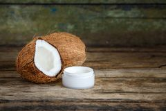 Coconuts with cosmetics cream on wooden background. Fresh whole and cut in half coconuts with coconut cosmetics cream on wooden background with copy space royalty free stock photo