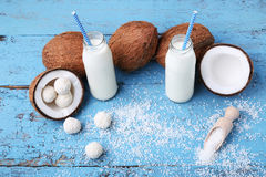 Coconuts. With flakes in scoop and bottle of milk on blue wooden table Stock Photo