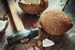 Coconuts and hammer on wooden table Stock Images