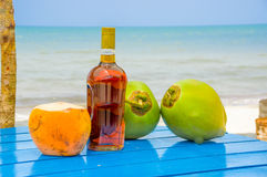 Coconuts and liquor bottle on table by the beach Royalty Free Stock Image