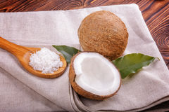 Coconuts and a spoon on a gray piece of cloth on a bright background. A wooden spoon full of coconut flakes. Nuts and green leafs. Close-up coconuts on a gray Stock Images