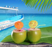 Coconuts straw cocktails in caribbean beach. Coconuts straw cocktails in tropical caribbean turquoise beach with boat Stock Photography