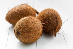Coconuts. Three whole not split coconuts, on a wooden white plank background. Some coconuts in the group Stock Image