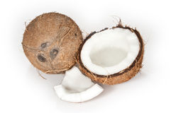 Coconuts on a white background. Two coconuts isolated on a white background. One of them is broken and filled with coconut milk Royalty Free Stock Images