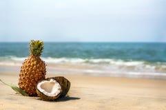 Cocos e abacaxis na areia pelo mar Fotografia de Stock