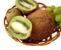 Cocos, grüne Kiwi und Trauben im Korb über weißem Hintergrund Lizenzfreie Stockfotografie