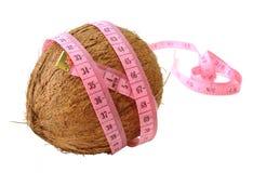 Cocos mit rosafarbenem Bandmaß über weißem Hintergrund (Konzept von ihm Stockfotografie