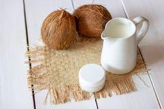 Cocos y leche de coco en un pote del metal Fondo de madera fotografía de archivo libre de regalías