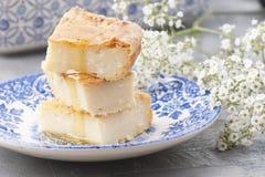 Cocotte en terre avec du fromage et le miel, sur un fond gris et des fleurs, l'espace libre pour le texte images stock