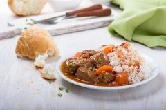 Cocotte en terre de boeuf et de légume servie avec du riz Photographie stock