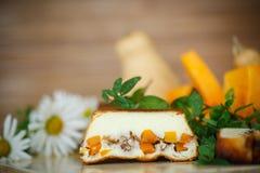 Cocotte en terre de fromage blanc avec des tranches de potiron et d'écrous Photographie stock